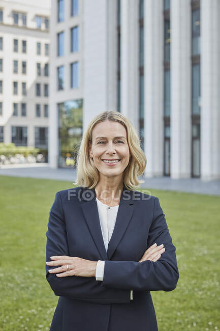 Portrait of confident businesswoman standing on lawn in the city — Stock Photo