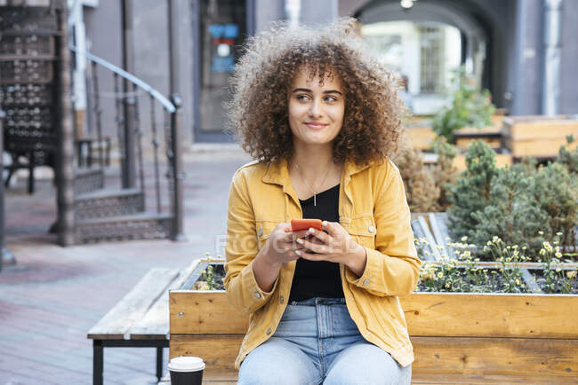Portrait of smiling teenage girl sitting on bench with coffee and mobile phone — Stock Photo