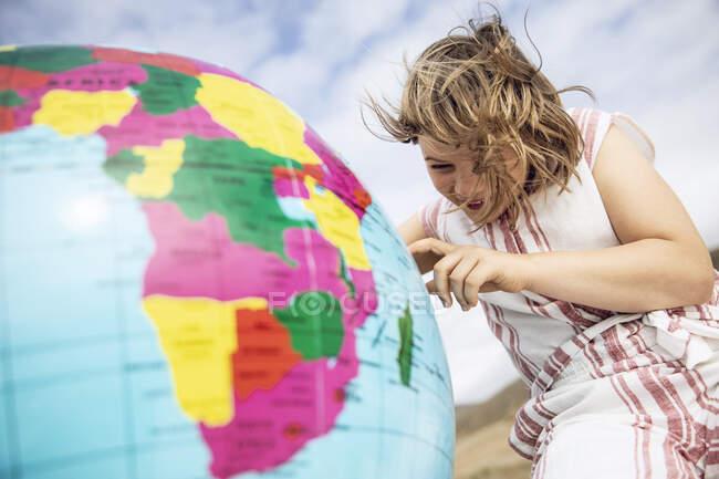 Маленька дівчинка вказує на надувну кулю. — стокове фото