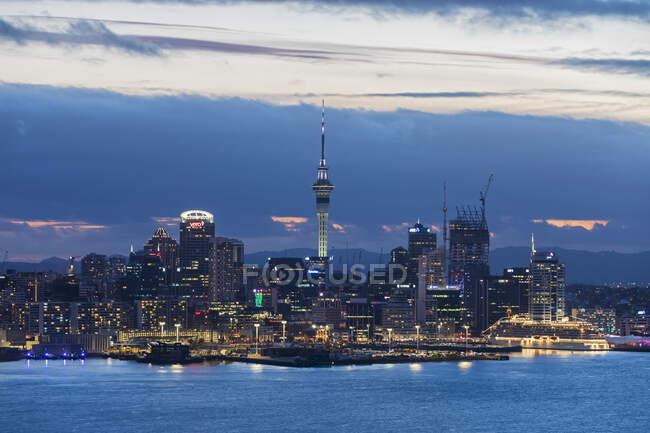 Illuminated modern buildings by sea against cloudy sky at dusk, Oceania, New Zealand — Stock Photo