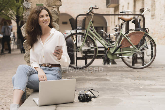 Smiling young woman with smartphone, camera and laptop outdoors — Stock Photo