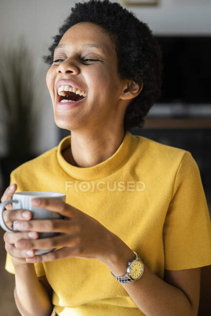 Laughing young woman holding mug at home — Stock Photo
