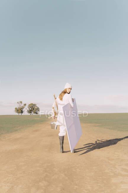 Молодая женщина несет мольберт и пустой холст на сухом поле — стоковое фото