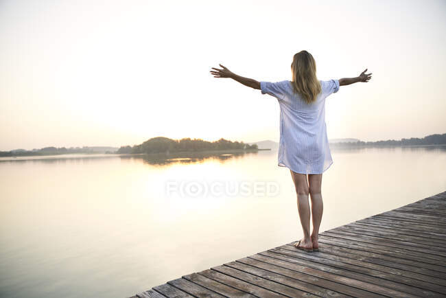 Rear view of mature woman standing on jetty at a lake at sunrise — Stock Photo