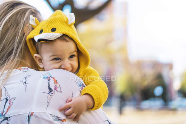 Мама носить хлопчика в парку. — стокове фото