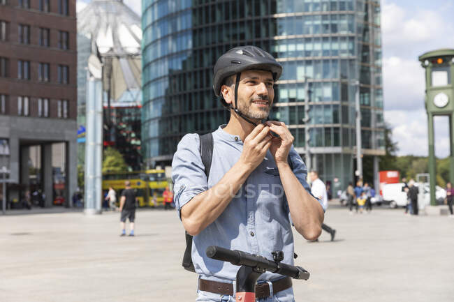 Man fastening the helmet before riding on electric scooter, Berlin, Germany — Stock Photo