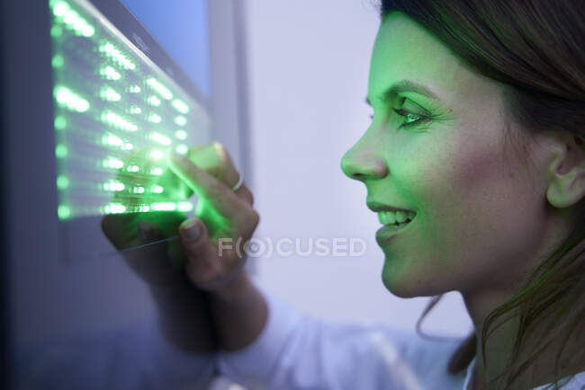 Close-up of smiling woman touching green led touchscreen — Stock Photo