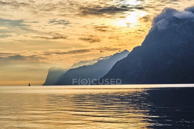 Italy, Trentino, Nago-Torbole, Silhouette of sailboat sailing near coastal cliffs of Lake Garda at moody sunrise — Stock Photo