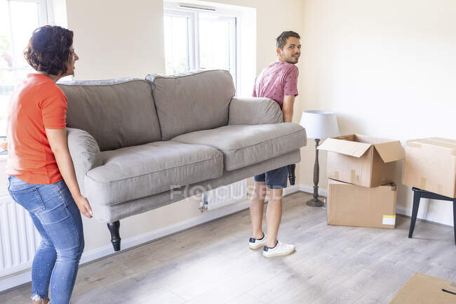 Couple moving into new home carrying a sofa — Stock Photo
