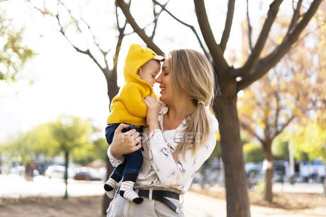 Щаслива мати з дитиною в парку. — стокове фото