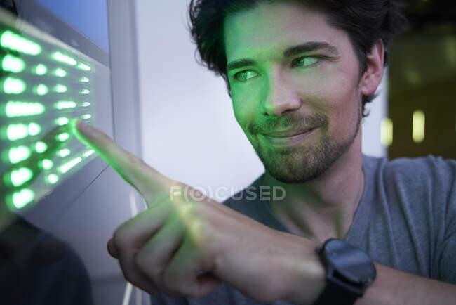 Primer plano del hombre sonriente tocando la pantalla táctil led verde - foto de stock