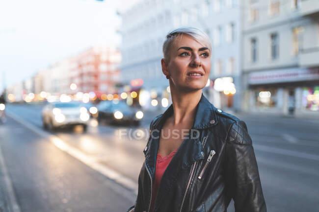 Retrato de mulher loira em pé à beira da estrada à noite, Berlim, Alemanha — Fotografia de Stock
