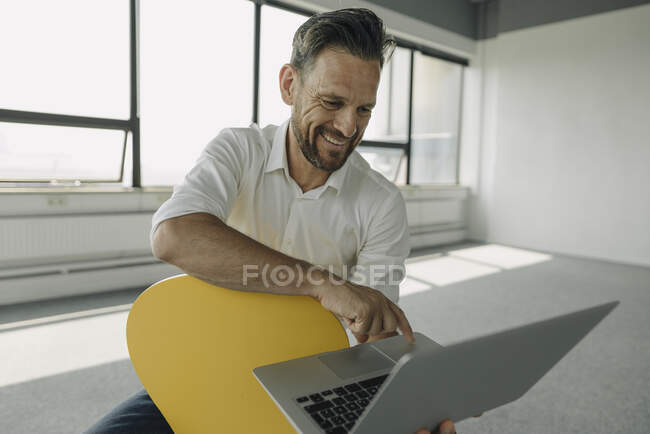 Smiling mature businessman using laptop in empty office — Stock Photo