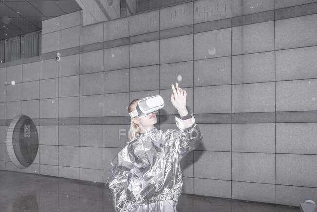 Girl in silver suit looking through VR goggles, watching her hand — Stock Photo