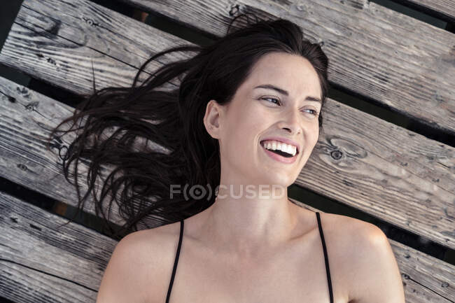 Portrait of laughing young woman relaxing on jetty — Stock Photo
