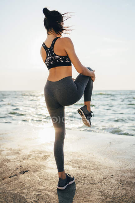 Вид сзади на женщину, растянувшую ногу на пирсе — стоковое фото