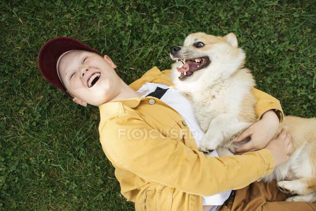 Niño con el galés Corgi Pembroke acostado en el prado - foto de stock