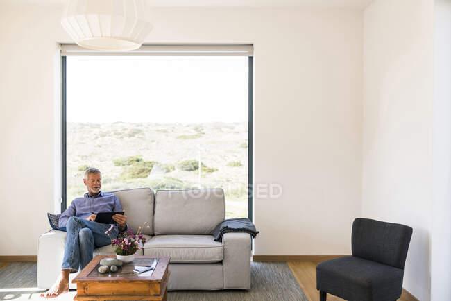 Старший чоловік користується планшетом на дивані вдома. — стокове фото