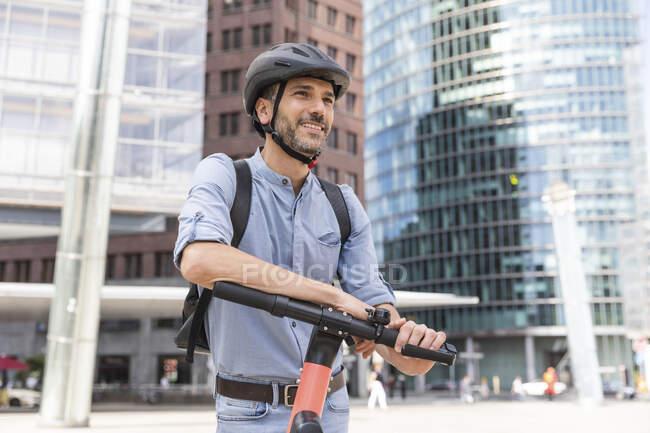 Homme souriant avec e-scooter sur la place de la ville, Berlin, Allemagne — Photo de stock
