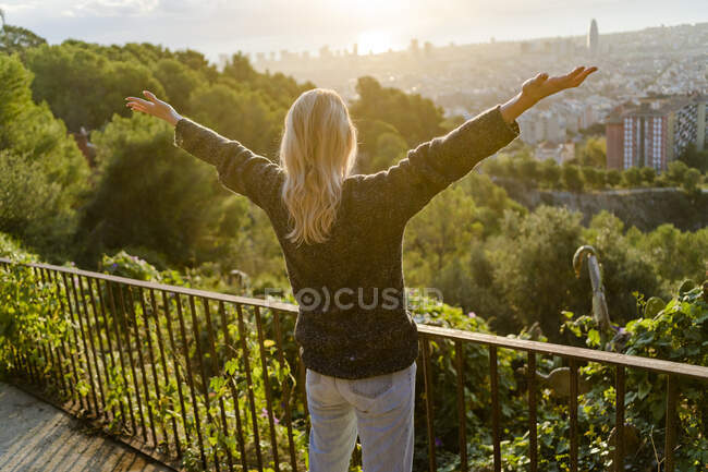 Rear view of carefree young woman standing above the city at sunrise, Barcelona, Spain — Stock Photo