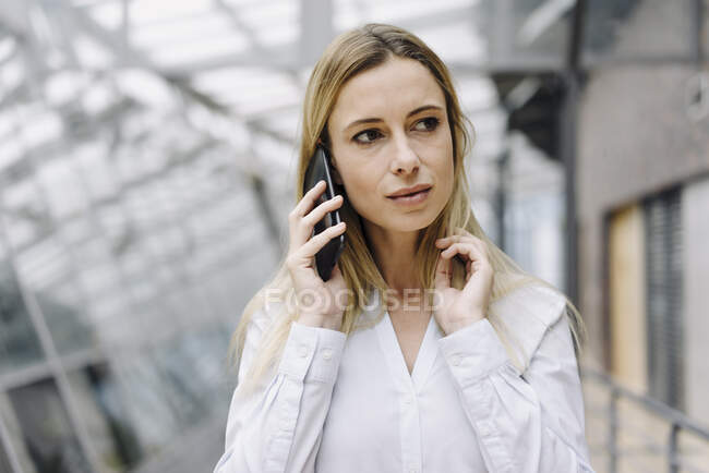 Portrait of a serious young businesswoman on the phone — Stock Photo