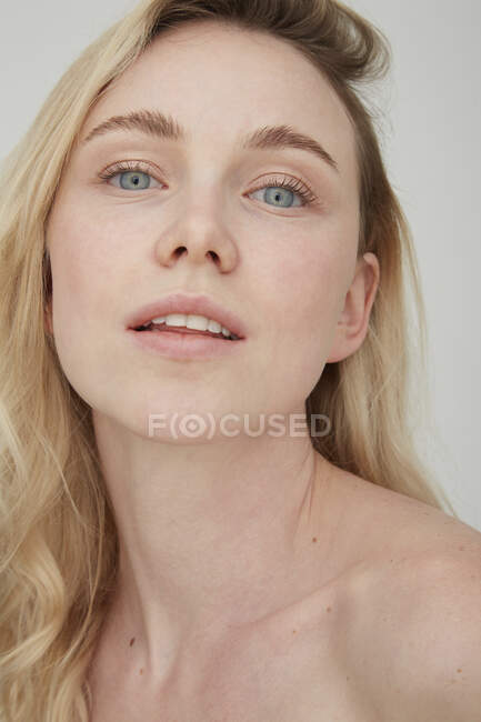 Portrait of blond young woman with blue eyes — Stock Photo