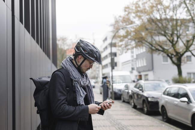 Молодий чоловік з велосипедним шолом і рюкзаком стоїть на тротуарі і дивиться на мобільний телефон. — стокове фото