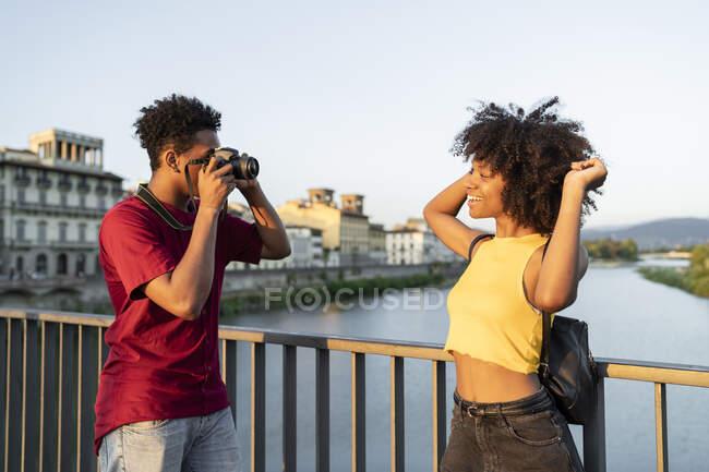 Молодой человек фотографирует свою девушку на мосту над рекой Арно на закате, Флоренция, Италия — стоковое фото