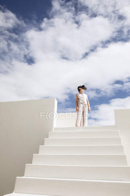 Girl standing on top of stairs, looking through VR goggles — Stock Photo