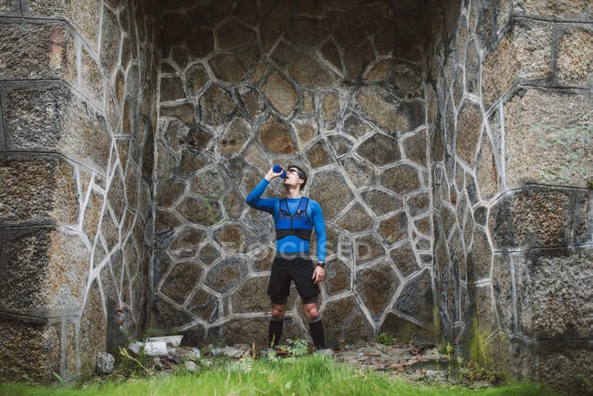 Trail runner standing at a wall drinking water — Stock Photo