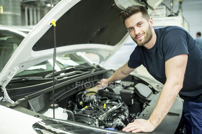 Портрет упевненого чоловіка, який працює над автомобілем на сучасній фабриці. — стокове фото