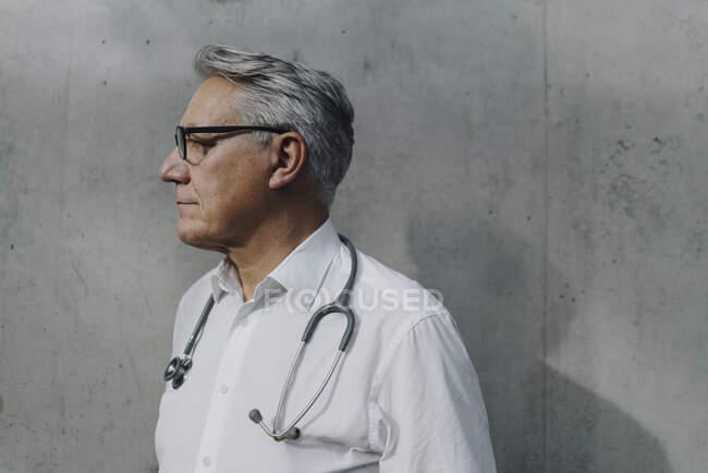 Médico senior pensativo en una pared de hormigón - foto de stock
