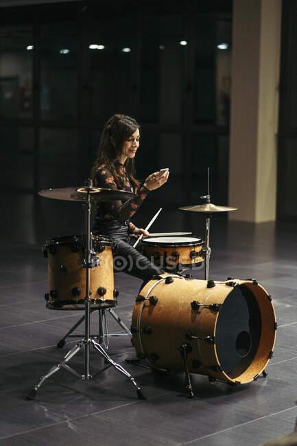 Mujer joven tocando la batería en el escenario - foto de stock