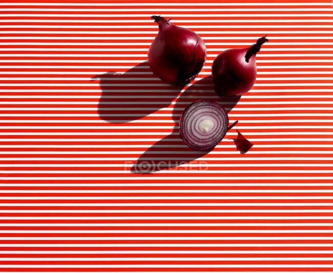 Vista de alto ângulo de cebolas na mesa listrada — Fotografia de Stock