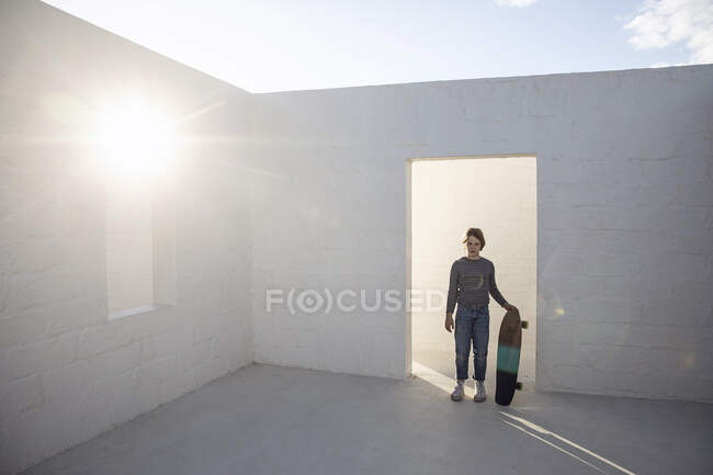 Ragazza con skateboard in piedi in uno spazio vuoto, illuminato dal sole — Foto stock