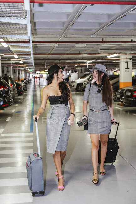 Two fashionable young women with baggage walking in airport car park — Stock Photo