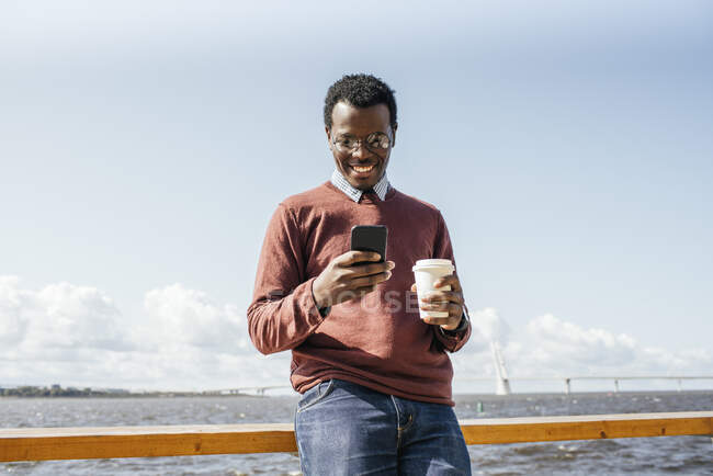 Young man standing at the sea, holding coffee, using smartphone — Stock Photo