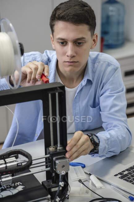 Student setting up 3D printer — Stock Photo