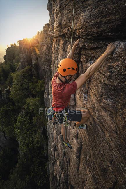 Чоловік, який піднімається на скелі Баттерт на заході сонця, Баден-Баден, Німеччина. — стокове фото