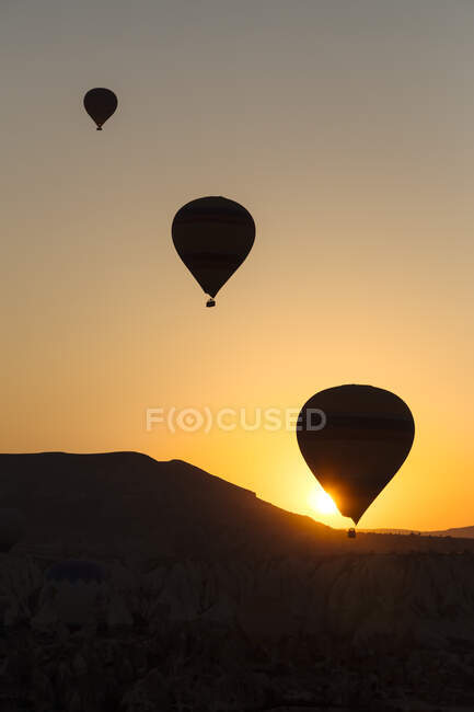 Silhouette hot air balloons flying over landscape during sunset at Goreme, Cappadocia, Turkey — Stock Photo