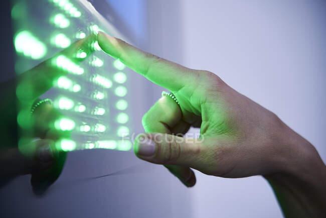 Detalle de dedo que toca la pantalla táctil led verde - foto de stock
