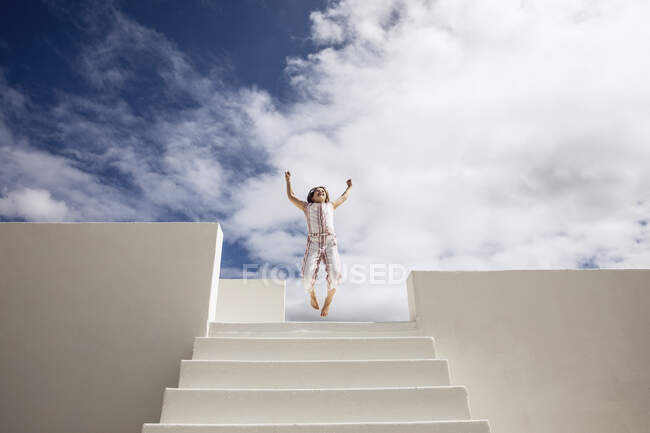 Little girl on top of stairs jumping for joy — Stock Photo
