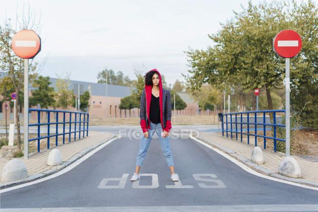 Retrato de jovem mulher com telefone celular em pé na palavra 'parar' na rua — Fotografia de Stock