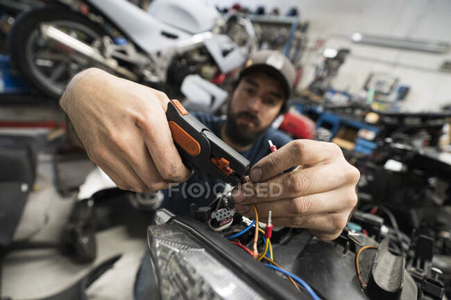 Mechanic in a repair garage repairing a motorcycle — Stock Photo