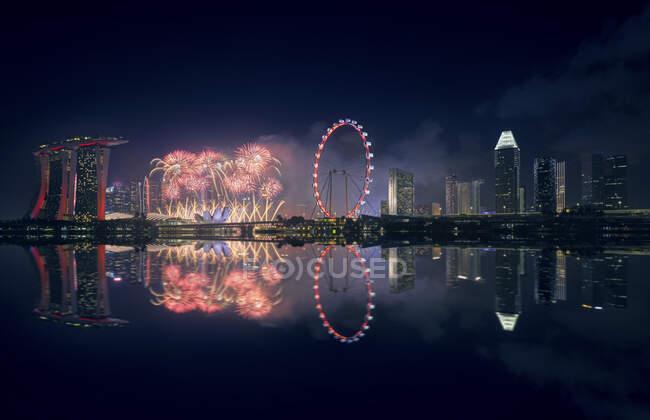 Сінгапур, нічний феєрверк між готелем Marina Bay Sands та освітленням коліс Ferris. — стокове фото