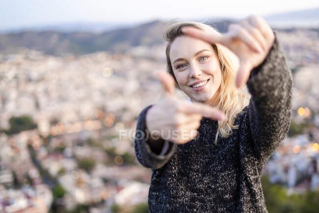 Ritratto di giovane donna che fa un dito al sorgere del sole sopra la città, Barcellona, Spagna — Foto stock