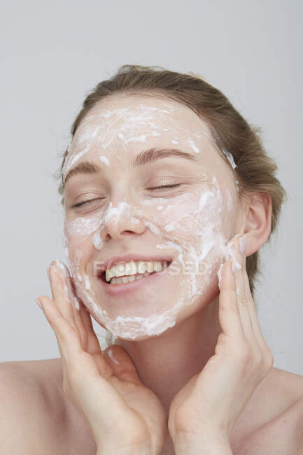 Portrait of blond young woman with eyes closed applying cream on her face — Stock Photo