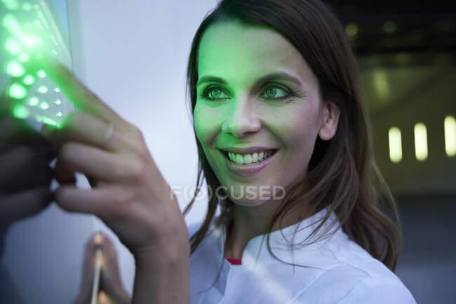 Primer plano de la mujer sonriente tocando la pantalla táctil led verde - foto de stock