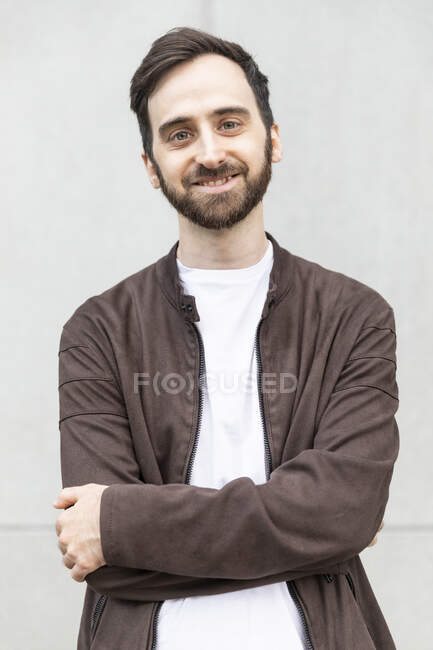 Bearded man smiling at camera, with arms crossed — Stock Photo