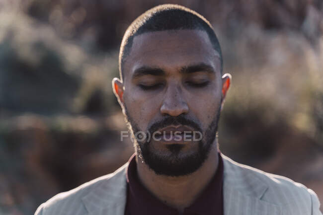 Portrait of young man with closed eyes outdoors — Stock Photo